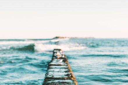 Titelbild Retreat an der Nordsee mit Suzanne Frankenfeld [Bildbeschreibung: Blick auf ein leicht aufgewühltes Meer mit Wellen über einen schmalen Steg hinaus. In der Ferne lässt sich unscharf ein flacher Felsen oder eine kleine Insel erkennen.]
