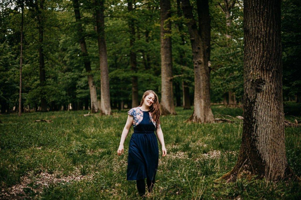 Titelbild zum Artikel zum Thema Selbstliebe lernen - abgebildet ist eine Frau (Suzanne Frankenfeld), die in einem Wald zwischen Bäumen steht und mit geschlossenen Augen lächelt