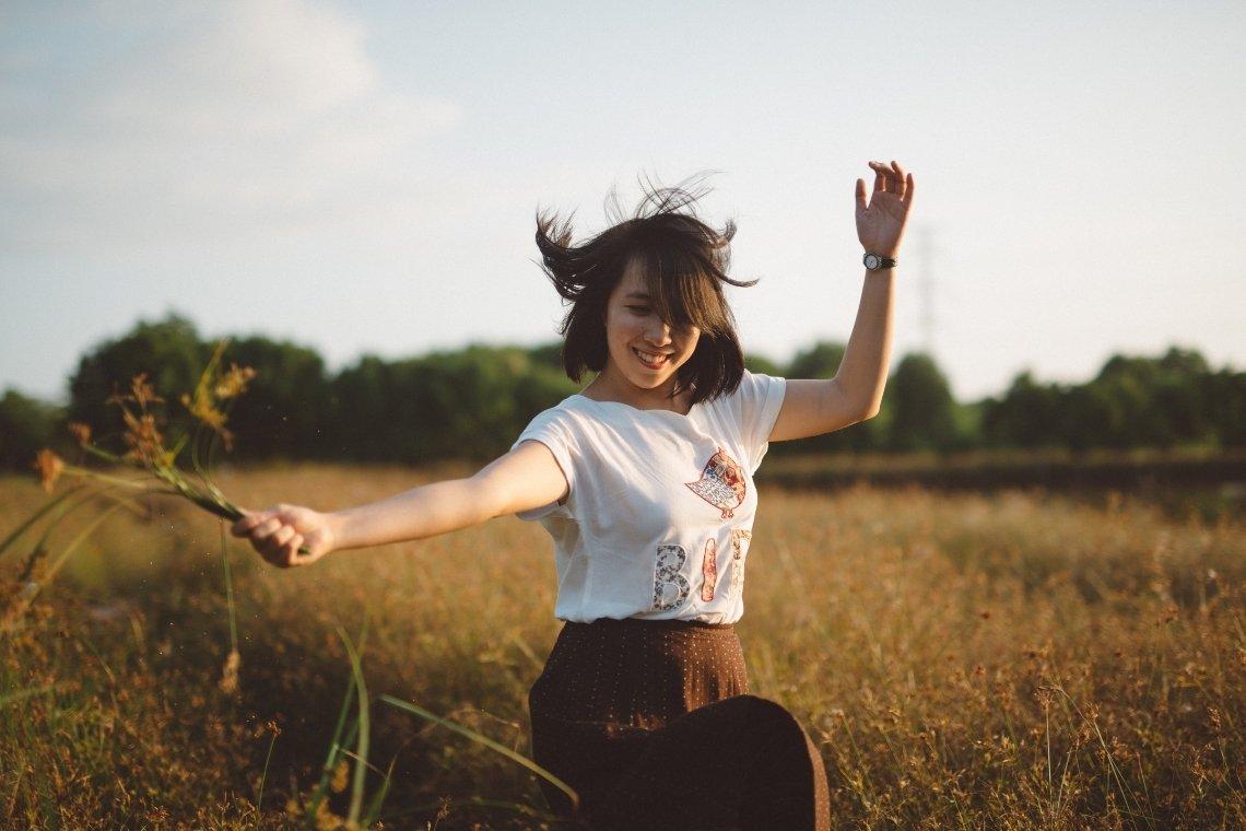 Kostenfreie geführte Selbstliebe Meditation - Bildbeschreibung: Eine junge Frau tanzt lächelnd in einem Feld voller hüfthoher Gräser.