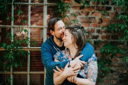 Wie das Home Office meines Mannes fast eine Beziehungskrise auslöste – und gleichzeitig ein großer Glücksfall für mich und uns war! [Bildbeschreibung: Eine Frau und ein Mann stehen sich umarmend vor einer Backsteinwand mit einem alten Fenster drin.]