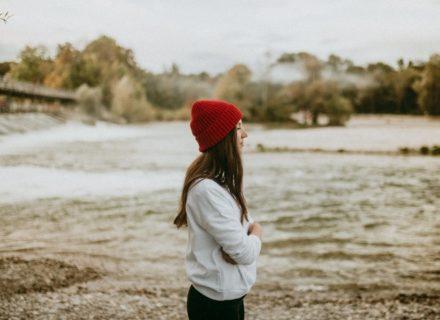 Spirituelles Business aufbauen - enttarnte Mythen & 7 Lehren von meinem Weg [Bildbeschreibung: Eine junge Frau mit einer auffallenden roten Mütze steht an einem Flussufer und scheint in die Ferne zu schauen]
