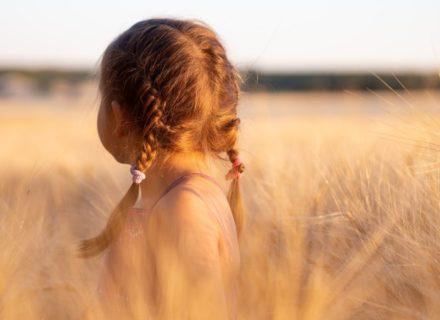 Lerne, Dein inneres Kind liebevoll zu versorgen und schau zu, welche positiven Effekte diese Arbeit auf Dein Leben hat! (Bildbeschreibung: Ein kleines Mädchen mit geflochtenen Zöpfen steht in der Abendsonne in einem Feld. Sie wendet sich von der Kamera weg, ihr Gesicht ist nicht zu sehen.)
